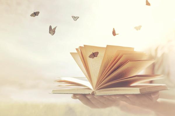 papillons qui s'envolent d'un livre ouvert tenu dans les mains
